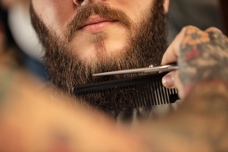 Barber shaving bearded hipster close up