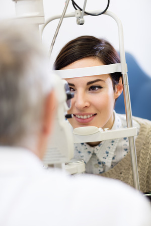 determines: Female patient on ophthalmoscope determines eye diopter Stock Photo