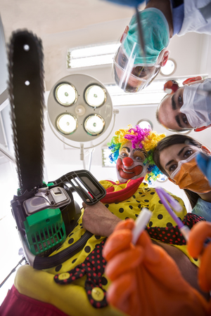 delusion: Nightmare delusion of dental operation with clown from horror holding chainsaw in bottom view