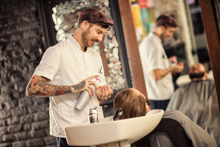 hairstylist: Hairstylist washing head of man with beard in barbershop