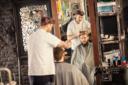 bearded man getting haircut by hairdresser while sitting in chair at barbershop Stock Photo