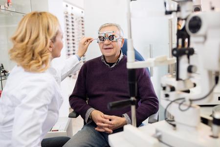 persona mayor: especialistas en óptica Vistas a la vista al paciente en la clínica de ojos Foto de archivo