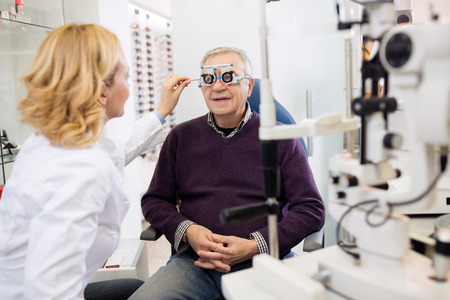 Optic specialists views eyesight to patient in eye clinic Archivio Fotografico
