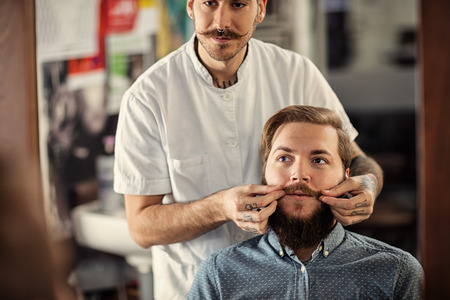skillful: Skillful male barber is serving his client mustache Stock Photo