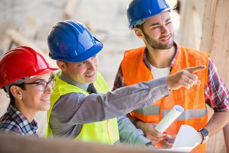Site manager uit te leggen aan architecten en wijzen op de plaats van de toekomstige gebouw Stockfoto - 53597092