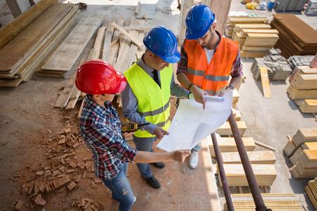 materiales de construccion: Arquitectos de consultoría entre sí acerca de plan de construcción rodeados de materiales Foto de archivo