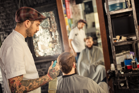 barbershop: Barber sprinkles a client with water at barbershop