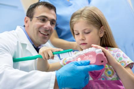 ambulant: In dental clinic dentist teaching girl how properly brush her teeth