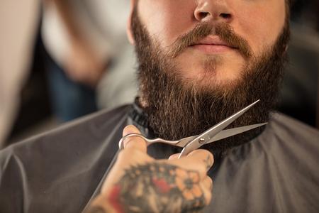 barber scissors: Barber with scissors shaving bearded man Stock Photo