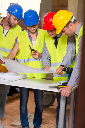 Male architect explaining building plan to colleagues at construction site Stock Photo