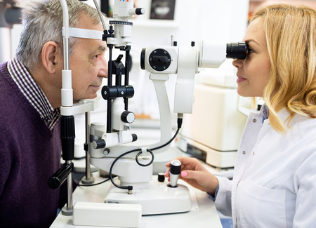 Female ophthalmic doctor check eyes to elderly man in eye clinic Stock Photo