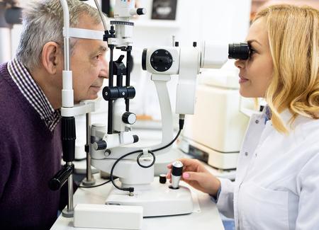 Vrouwelijke oogheelkundige arts check ogen bejaarde in oogkliniek