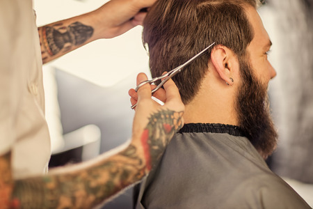male hair: overside haircut by a professional barber with scissors Stock Photo