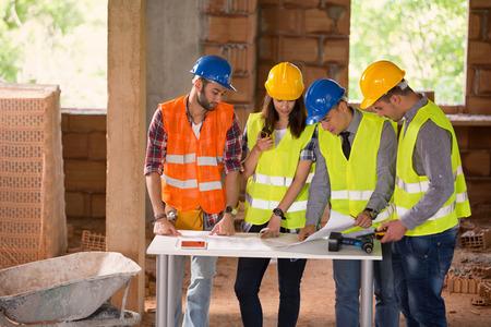 若者のグループ エンジニア建設現場で勉強のブルー プリント