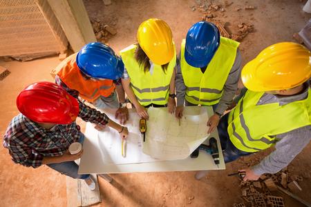 건설 현장에서 계약을하는 건축가의 다채로운 하드 모자의 상위 뷰