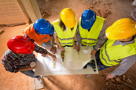 hard hats: Top view of colorful hard hats of architects making agreement at construction site Stock Photo