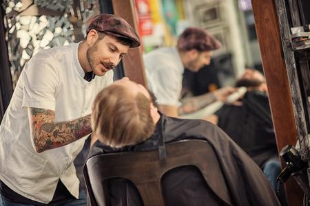 skillful: professional skillful barber shaving beard on customer