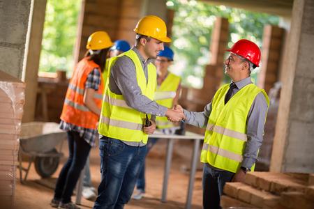建築家と新しい建物の叙任の取り引きとのハンド シェークを作る
