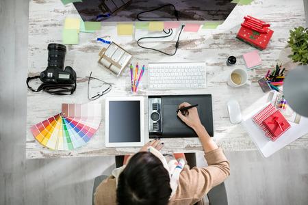 Kobieta, projektant pracy na stole pióro w biurze widok z góry