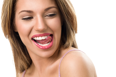 Sensual woman biting tongue with perfect teeth