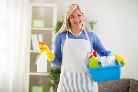washbowl: Smiling female wears cleaning products in plastic washbowl Stock Photo