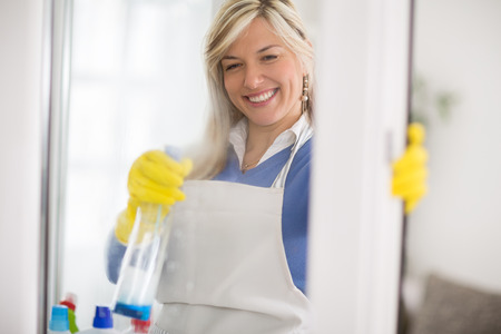 cleaning services: Close up of female from cleaning service professionally cleans window