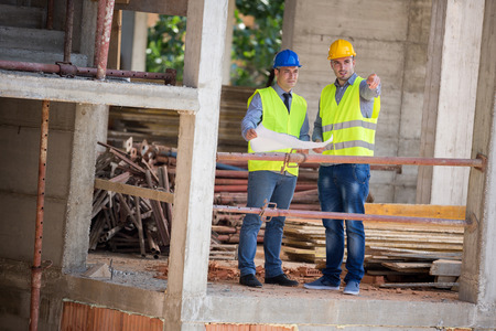 construction workers: Two male architects show building place and discus with colleague architect, male Stock Photo