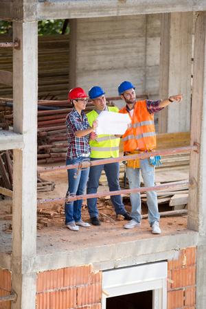 industrial site: Group of architects discussing and planning future building on construction site Stock Photo
