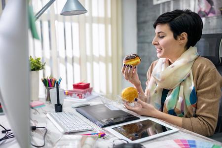 オフィスでドーナツを食べて満足しているデザイナー