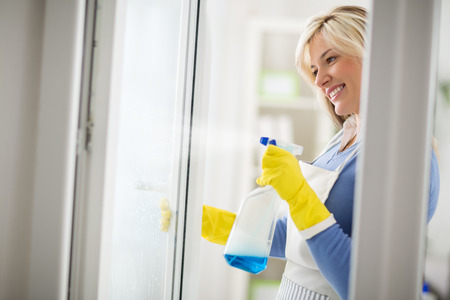 appropriate: Housewife easy wash windows with appropriate cleanser in bottle with spray Stock Photo