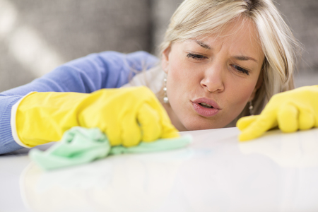 stain: Pretty cleaning woman removes stains from table Stock Photo