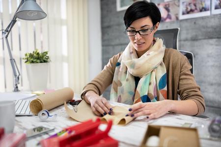 designer: woman designer packing gift for client