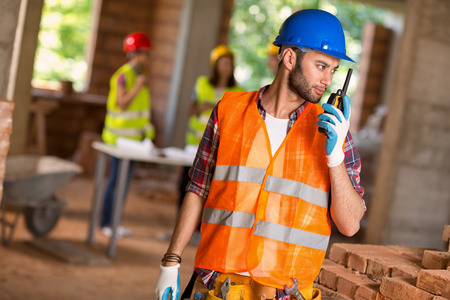 walkie talkie: Young construction worker talking on walkie talkie at building site Stock Photo