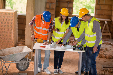 hat project: Experienced architect explain details of construction plan to colleagues at building site Stock Photo