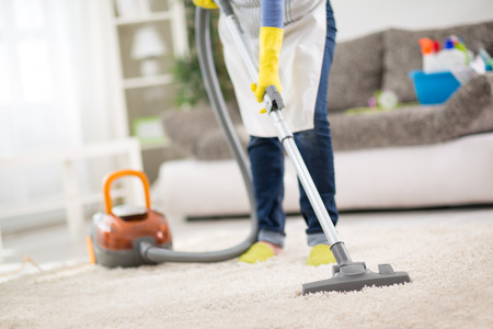 Housewife from cleaning service cleans carpet with vacuum cleaner