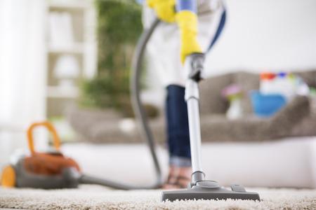 Vrouw zuigt tapijt met stofzuiger Stockfoto