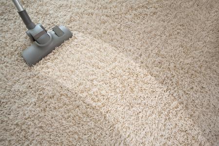 Aspirar la alfombra áspera en la sala con el aspirador
