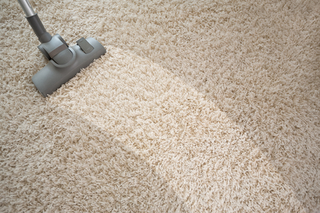 Vacuuming rough carpet in living room with vacuum cleaner