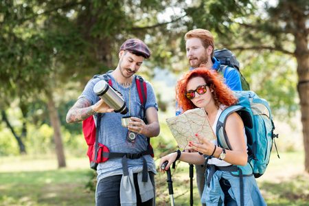 thermos: Sports people hiking with backpack, map, thermos and hiking sticks through forest Stock Photo