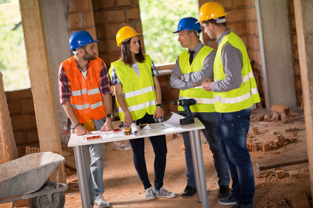 agreeing: Group of architects discussing and agreeing about blue print on site Stock Photo