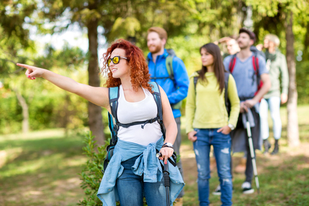 green nature: Girl in group of hikers pointing something in woods