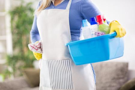 Jonge vrouw bereidt chemische producten voor om huis schoon te maken