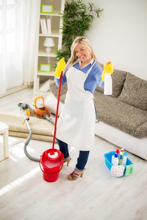 productos quimicos: Ama de casa sonriente que presenta con los productos de limpieza del hogar y qu�mica de la fregona