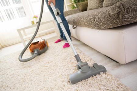 personal de limpieza: Alfombra de la limpieza con aspiradora en la sala de estar Foto de archivo