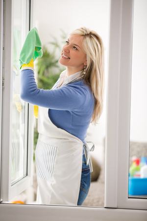 Housewife clean window glass and make spring cleaning