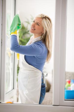 Hausfrau sauber Fensterglas und Frühjahrsputz machen