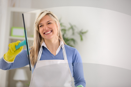 Close up of smiling young female wash windows in house Reklamní fotografie
