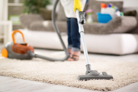 Close up of vacuuming carpet with vacuum cleaner Stock Photo