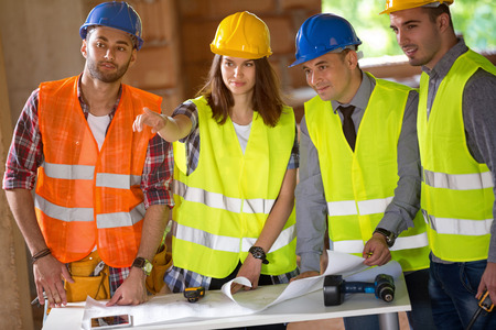 female engineer: Group of architects agreeing about schedule on construction site