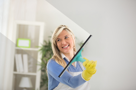 sweep: Young housekeeper sweep window glass